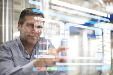 Man using transparent touchscreen device - FKF001760