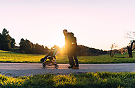 Couple on a walk with their baby in the stroller at sunset - GEMF000798