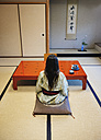 Japan, Uji, back view of woman wearing yukata drinking tea in a traditional Japanese room - GEM000802