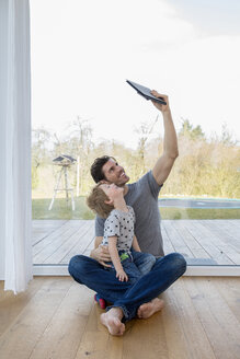 Father and son sitting on floor using digital tablet - FMKF002531