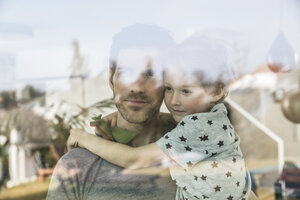 Father and son looking out of window - FMKF002564