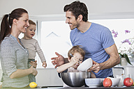 Family with two kids preparing food in kitchen - FMKF002597