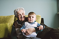 Old woman and her great-grandson sitting on the couch - RAEF000958