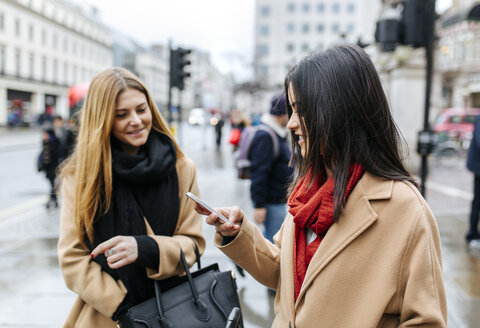 UK, London, Two friends exploring the city, using smart phone - MGOF001562