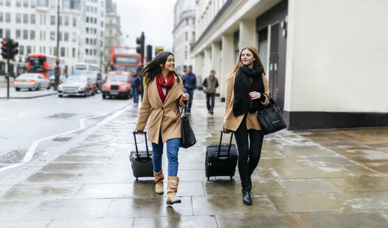UK, London, Two friends exploring the city, arriving with trolley bags - MGOF001565