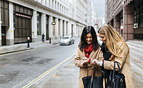 UK, London, Two friends exploring the city, checking smart watches - MGOF001568