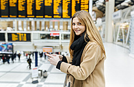 UK, London, Young woman using mobile phone at train station - MGO001571