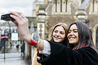 UK, London, Two friends exploring the city, photographing selves in front of Southwark Cathedral - MGOF001577
