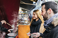 UK, London, Young couple trying punch at market stall - MGOF001580