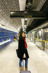 UK, London, Young woman standing at train station - MGO001583