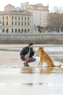 Spain, Gijon, man talking with his dog on the beach - MGOF001595