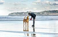 Spain, Gijon, man with his dog on the beach - MGOF001598