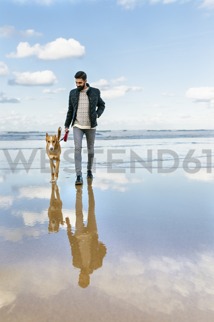 Man walking on the beach with his dog - MGOF001601 - Marco Govel/Westend61