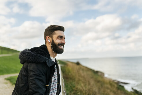 Portrait of bearded man listening music with earphones - MGOF001607
