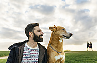 Portrait of bearded and his dog on a meadow - MGOF001610