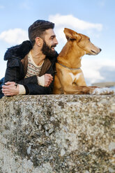 Man and his dog lying side by side on a wall - MGOF001616