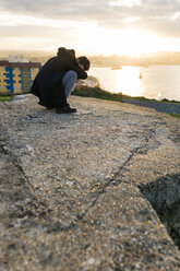 Spain, Gijon, man crouching on a wall at evening twilight covering face with his arm - MGOF001619