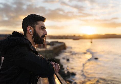 Spain, Gijon, bearded man listening music with earphones at sunset - MGOF001622