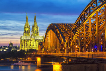 Germany, Cologne, view to lighted Cologne Cathedral with Hohenzollern Bridge in the foreground - TAMF000416
