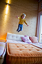 Little boy jumping on the couch at home - ZOCF000003