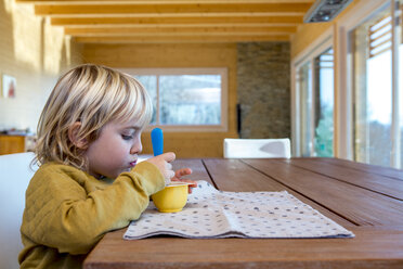 Little boy sitting at wooden table eating something - ZOCF000009