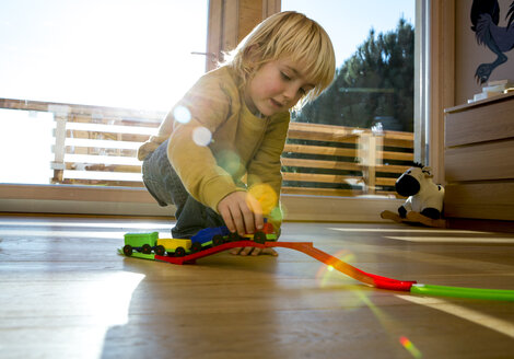 Little boy playing with toy train on the wooden floor at home - ZOCF000015