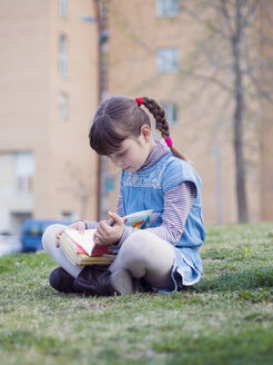 Little girl sitting on a meadow reading a book - XCF000066