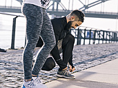 Germany, Cologne, Young couple, workout, man tying shoes - MADF000866