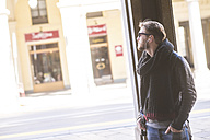 Man with sunglasses and earphones watching something - SIPF000263