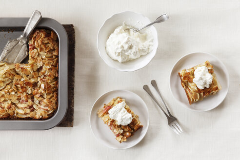 Pieces of whole meal apple pie with sliced almonds and whipped cream - EVGF002859