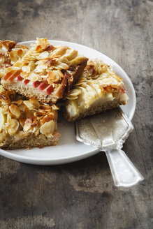 Pieces of whole meal apple pie with sliced almonds on a plate - EVGF002862
