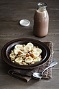 Dish of banana oatflakes granola and a bottle of cocoa - EVGF002868