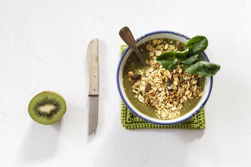 Bowl of green smoothie with mix of oatflakes and granola, kitchen knife and half of kiwi - EVGF002874