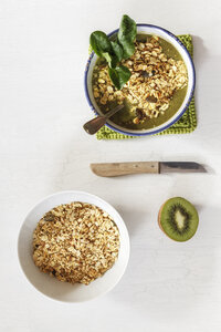 Bowl of green smoothie with mix of oatflakes and granola - EVGF002886