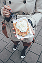 Belgium, Antwerp, young woman eating Belgian waffles on the street - RTBF000027