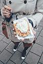 Belgium, Antwerp, young woman eating Belgian waffles on the street - RTBF000027