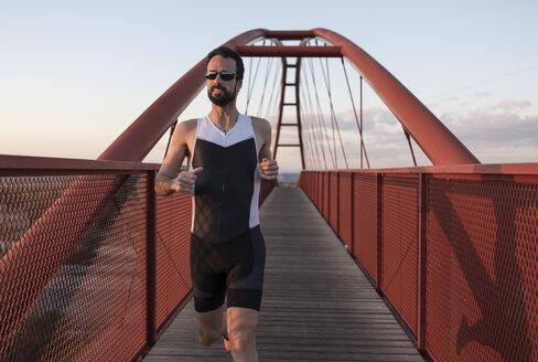 Runner training on a bridge at twilight - JASF000559
