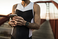 Runner using smartphone on a bridge, partial view - JASF000562