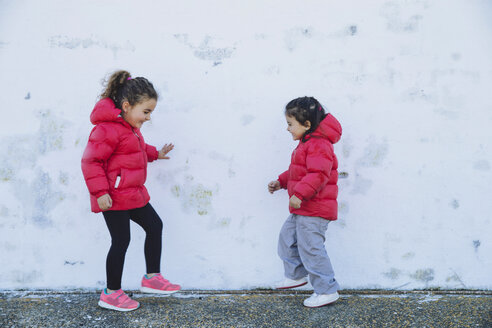 Two little girls dancing in front of a wall - ERLF000151