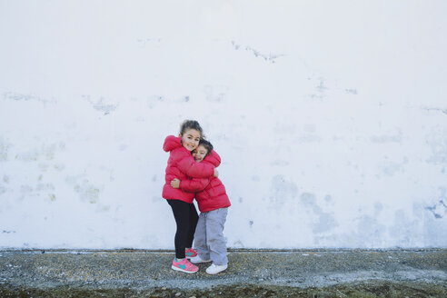 Two happy little sisters hugging each other in front of a wall - ERLF000154