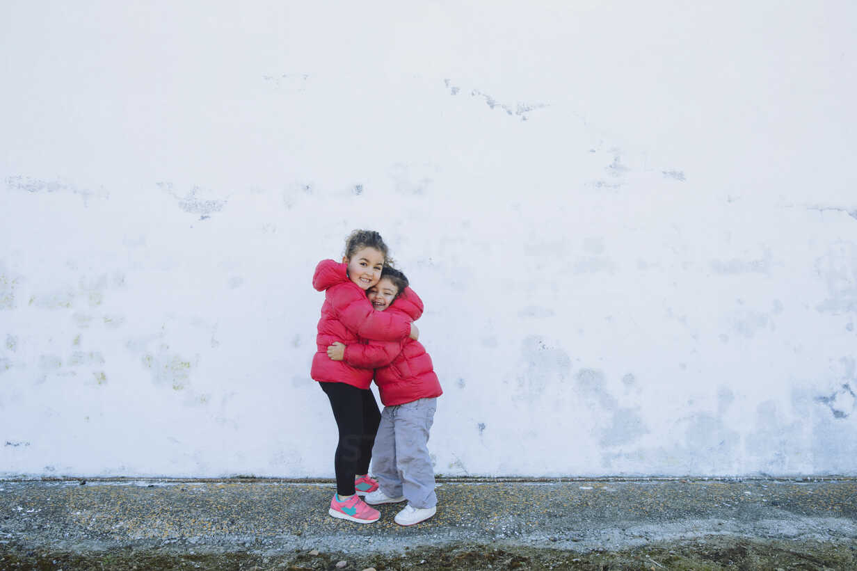 Two happy little sisters hugging each other in front of a wall - ERLF000154 - Enrique Ramos/Westend61