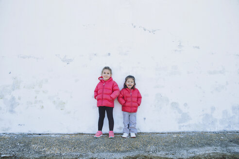 Two little girls pulling funny faces in front of a wall - ERLF000157