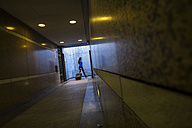 Young woman with rolling suitcase walking in an underpass - SIPF000278
