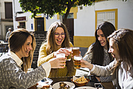Four happy friends toasting with beer in a street cafe - KIJF000244
