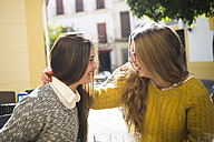 Two laughing young women in a street cafe - KIJF000247