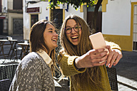 Laughing young woman taking a selfie with her friend at street cafe - KIJF000250