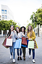 Group picture of four friends with shopping bags on a street - KIJF000259