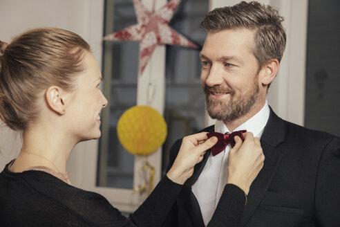 Couple preparing for New Year's Eve party, fastening bow tie - MFF002915