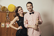 Couple holding bottle of Champagne on New Yera's Eve - MFF002918