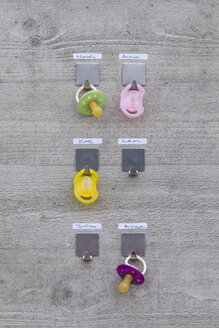 Pacifiers hanging on concrete wall with name tags - WDF003579